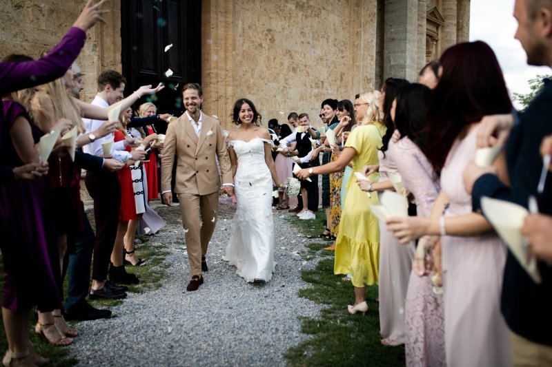Petals and rise tossing to newly-wed couple outside the san biagio church montepulciano - wedding planner tuscany