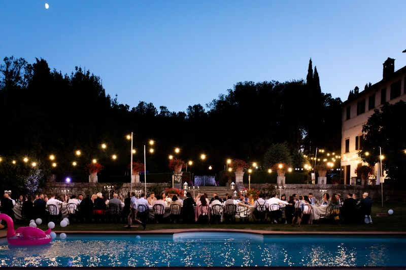 Outdoor dinner under the bulb light and by the pool - wedding planner siena