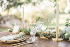 Minimalistic mise en place with golden cladlesticks and greenery
