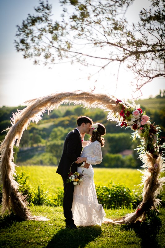 Round arch with pampas and shades of red with vineyard background - wedding planner siena
