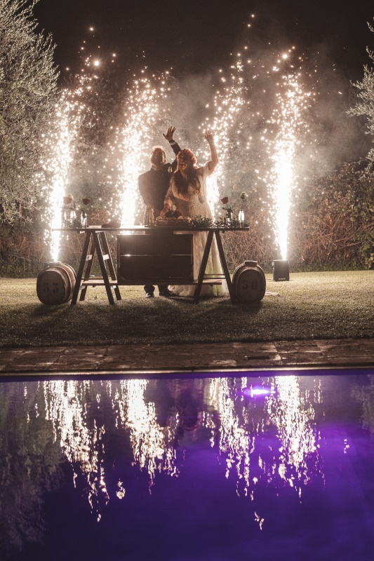 Wedding cake cutting by the pool with fireworks at the background