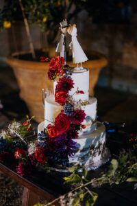 Tiered wedding cake with red and blu flowers - wedding planner tuscany