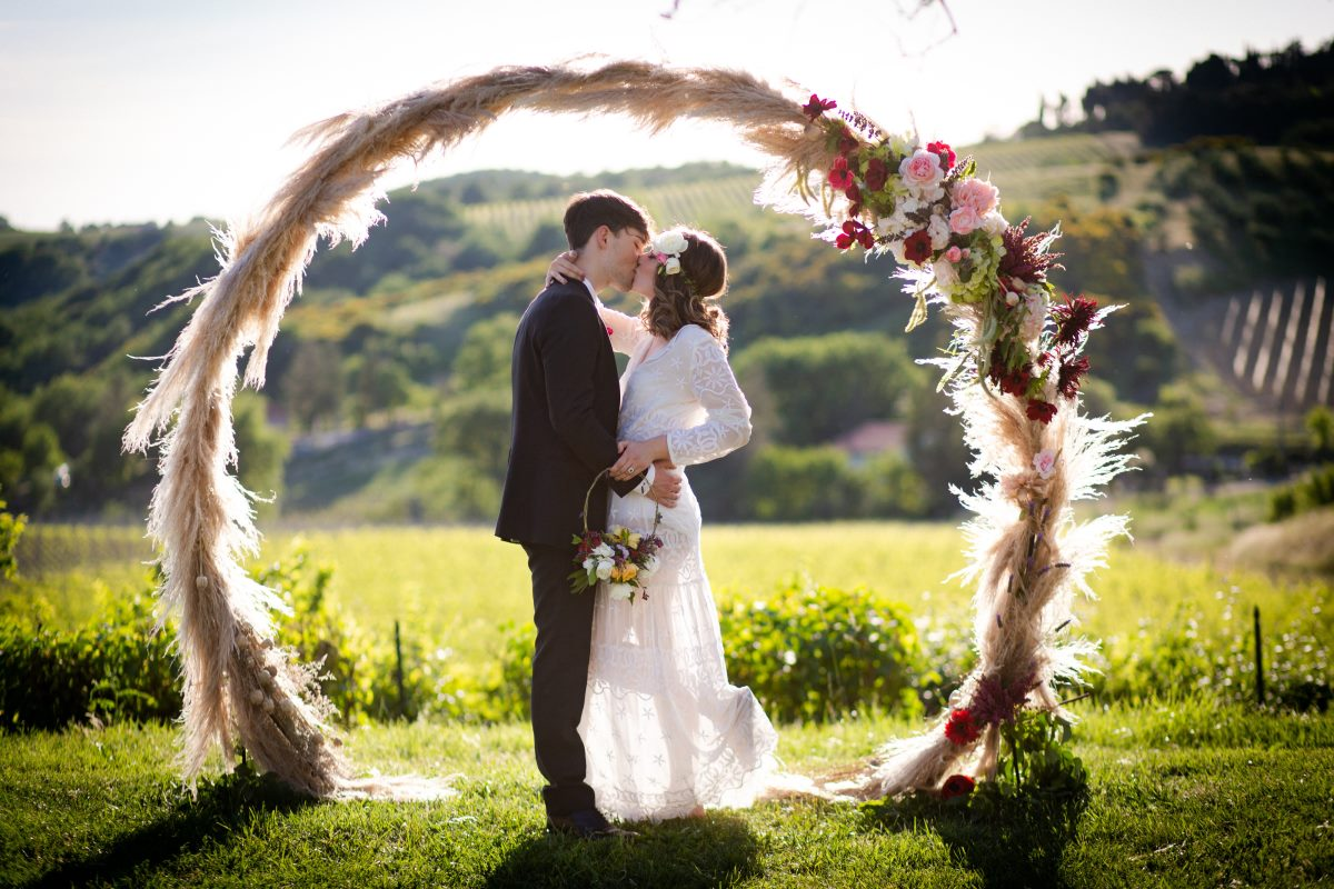 Wedding ceremony in the vineyards with romantic pampas arch in tuscany